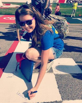 Autographing the Start/Finish line at Richmond Raceway during a NASCAR race in 2017